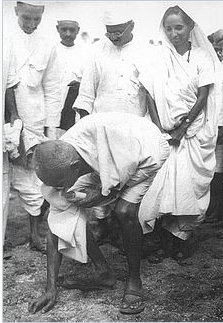 Gandhi scooping a handful of salt at the end of the Dandi March